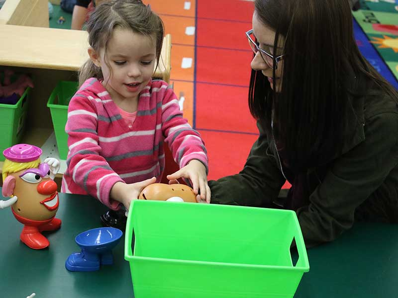 a teacher showing a girl student Mr. Potato from toys story