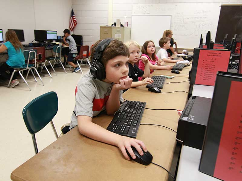 a boy student in the front of the computer learning