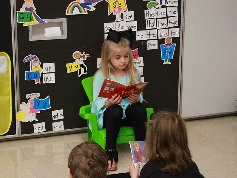 girl student reading a book in the front of the classroom