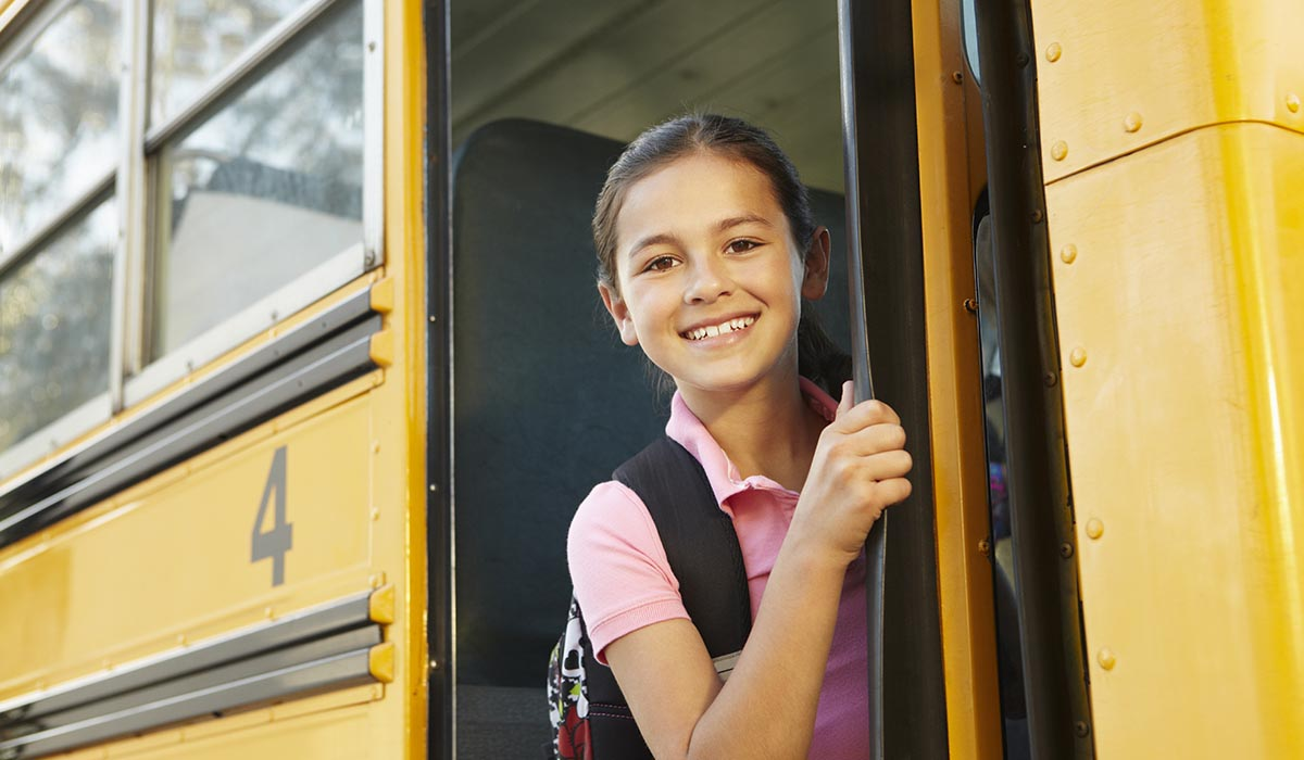 Girl student inside school bus smiling